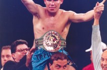 Boxer Julio Cesar Chavez is held aloft by another man and Chavez holds up his hands in a sign of victory.