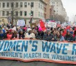 """A large group of women carry many signs, including a large banner that reads """"The Women's Wave Rises: 2019 Women's March on Washington."""""""