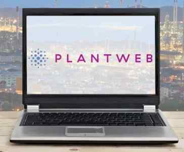 laptop on wooden table with oil refinery background