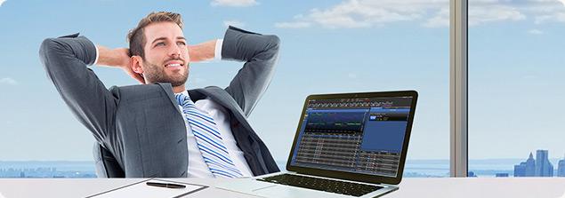 Trader en position relax a son bureau avec un pc portable devant lui