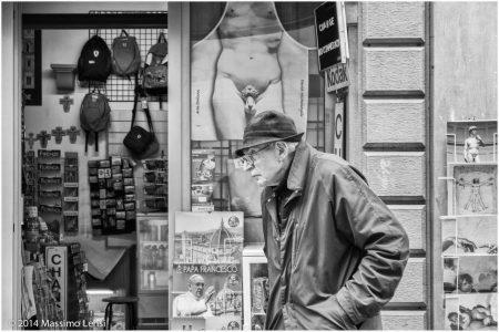 Un anziano signore cammina con lo sguardo fisso sulla strada, sullo sfondo la vetrina di un negozio di souvenir espone alla rinfusa crocifissi, immagini del papa e grembiuli stampati con le pudenda del Davide di Michelangelo