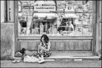 Una bimba accoccolata a riposare sotto la vetrina della pasticceria Scudieri a Firenze.