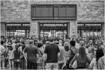 Folla di turisti assiepati in piedi nell'atrio della stazione di Santa Maria Novella, a suo tempo concepita da Michelucci per accogliere offrendo comodità e ampi spazi.