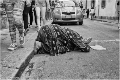 Una mendicante accucciata in terra chiede l'elemosina in una via del centro di Firenze, sfiorata dai piedi dei passanti che la ignorano.