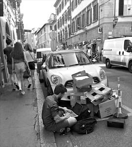 Un turista con il suo laptop seduto sul marciapiede in via Nazionale accanto a un mucchio di cartoni.