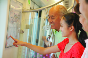 Young Asian girl and older Asian man pointing to transit map