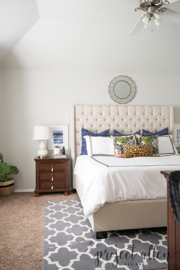 An eclectic bedroom with navy pillows, schumacher pillows, leopard lumbar pillow, Black and white greek key bedding, tufted wingback upholstered bed. Agate art and double gourd lamp. white curtains, Sherwin Williams Respose Gray, Sunburst Mirror. Nightstand with Tassels. wood bead garland, fretwork rug, fiddle leaf fig in basket