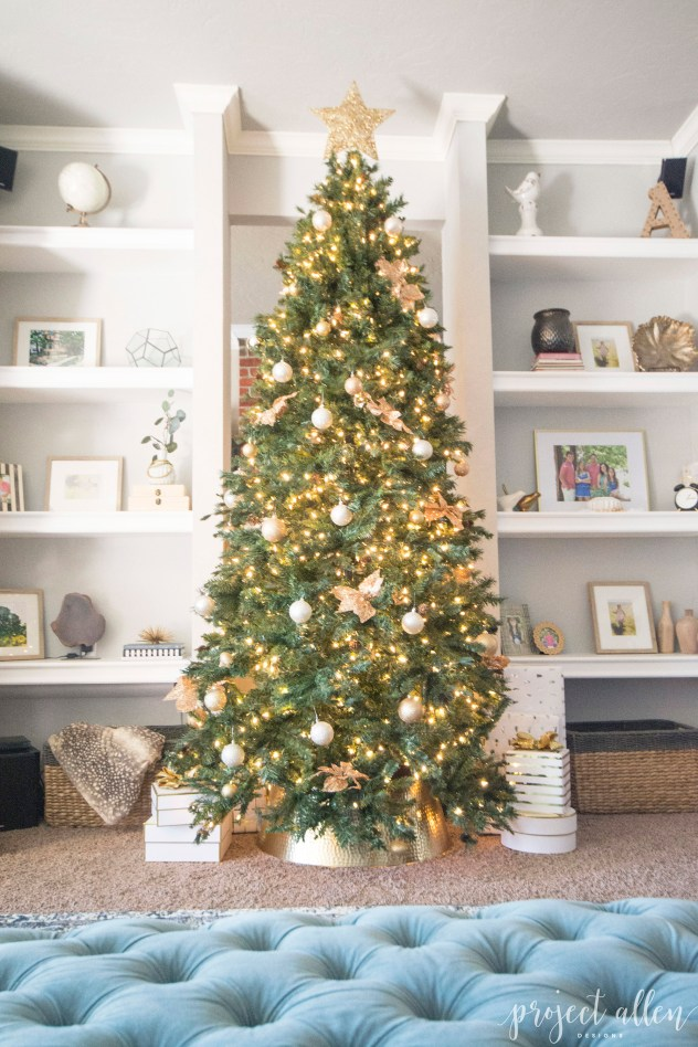 Modern Glam Christmas tree with gold ornaments, brass tree collar, glittered magnolia leaves and white and gold Christmas gifts tadd the perfect touch to these custom built-ins.