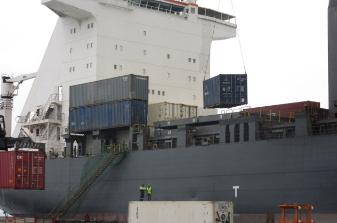 A container being loaded onto a vessel.