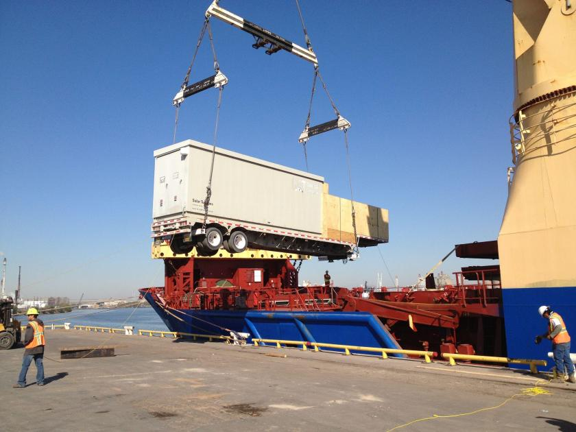 Loading a truck container onto a ship.