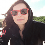 A selfie taken by a dark haired girl, wearing red sunglasses and a black hoodie