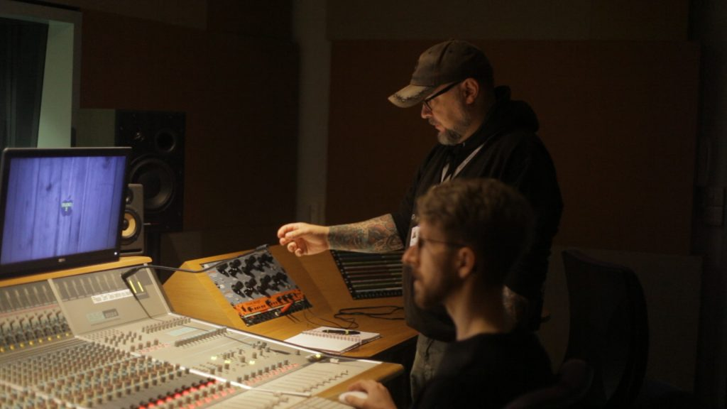 A photo of 2 men in front of a mixing desk