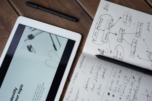 A tablet with a pen over a notebook full of flowcharts