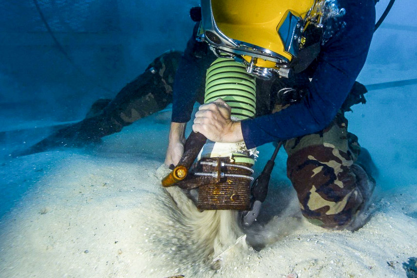 Navy Diver working vacuuming sand underwater during MIA recovery Palau