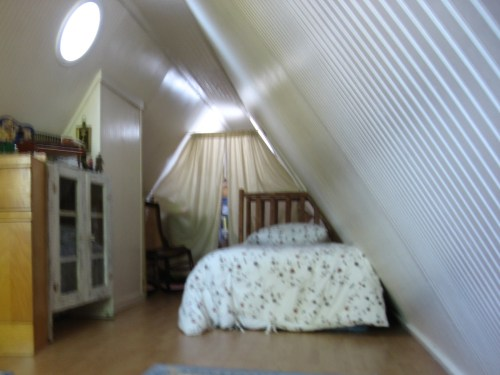 Project: Turning the Attic into a Playroom - There is room for a single bed, just the boxspring and mattress on the floor. The curtain hides storage on the other side.