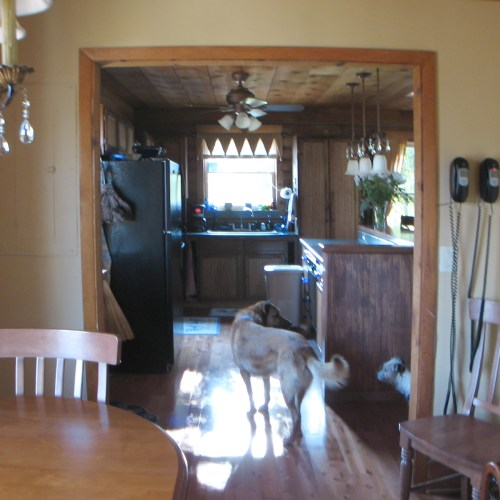 Log Cabin Kitchen Before & After: The window, sink and cabinets are centered.