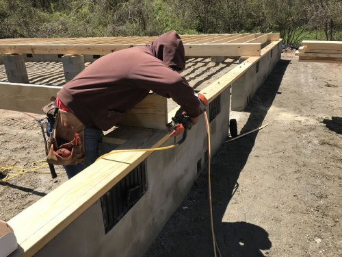 Nailing in the joists with a pneumatic nail gun - Building our Schumacher Home