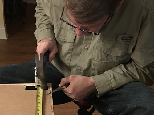 Cliff is assembling a Hemnes dresser from Ikea. He uses needle nose to hold the little nail so he doesn't hammer his fingers. - Getting Settled and Enjoying Spring – Project Small House
