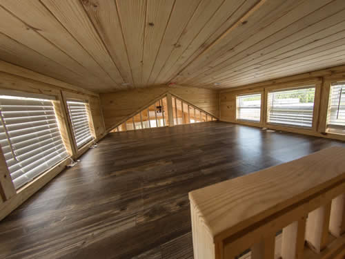 Inside the loft of a log cabin tiny house