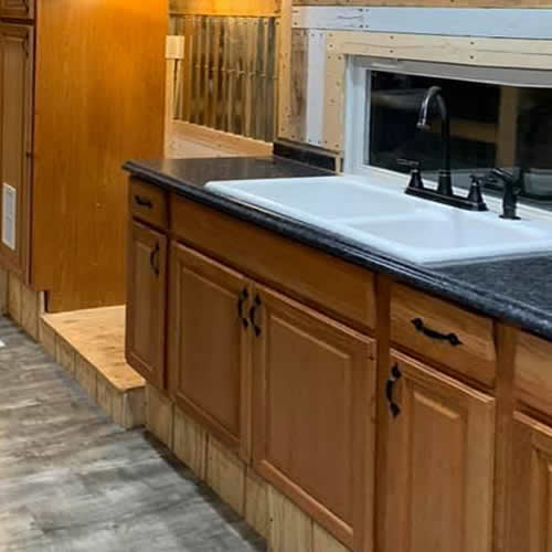 Oak kitchen cabinets, white sink, bronze faucet and sprayer