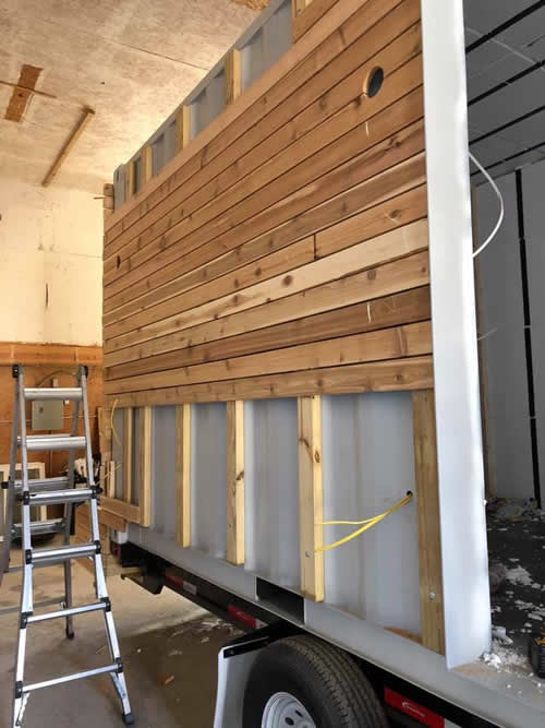 The outside of the container house is clad in natural cedar wood.