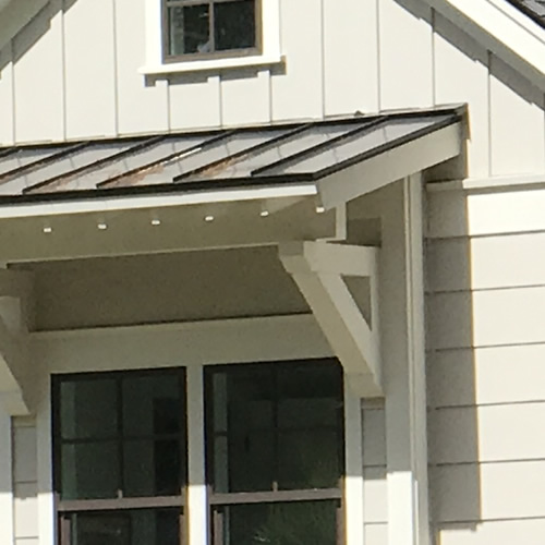 Craftsman style brackets support the metal roof over the window.