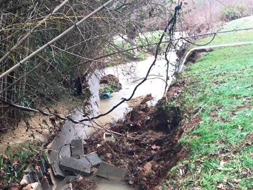 The retaining wall collapsed, blocking the original stream flow.