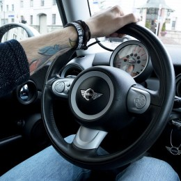A person with tattoo holding the steering wheel