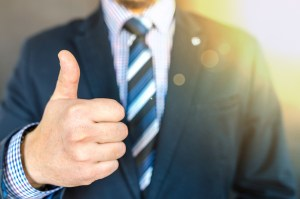 Person in a suit holding a thumbs up