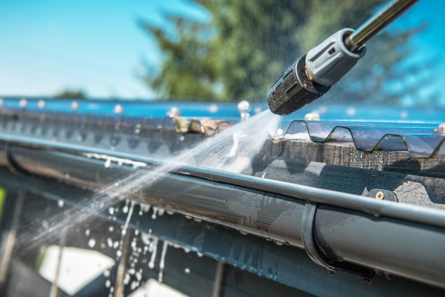 Pressure Washer Cleaning Commercial Gutters During Fall Maintenance For Commercial Properties