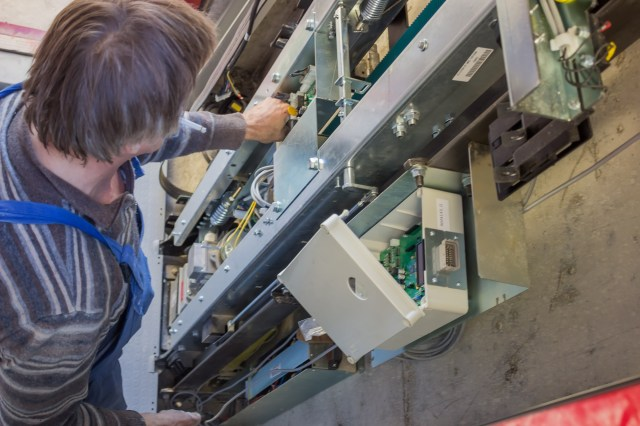 Elevator Mechanic Working On Elevator Control Panel Doing Service Work For An Independent Elevator Contractor