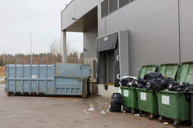 Trash Compactor And Overflowing Dumpsters Behind Apartment Building For Popularity of Valet Trash Surges Amid COVID-19 Pandemic Blog Post