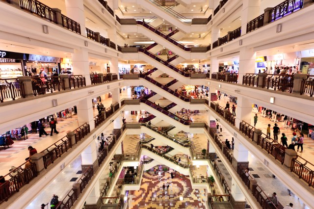 Busy Shopping Mall With Multiple Escalators And Floors
