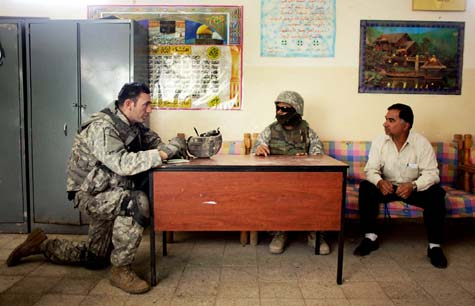 In this April 17, 2007, photo, Sgt. 1st Class Jerry Byrd of the 82nd Airborne Division talks to a Baghdad schoolmaster with the help of an Iraqi interpreter (center). (Joe Raedle/Getty Images)