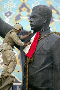 Cpl. Edward Chin affixes an Iraqi flag around the neck of the statue of Saddam Hussein before it is torn down in Bagdad on April 9, 2003. (Laurent Rebours/AP Photo)