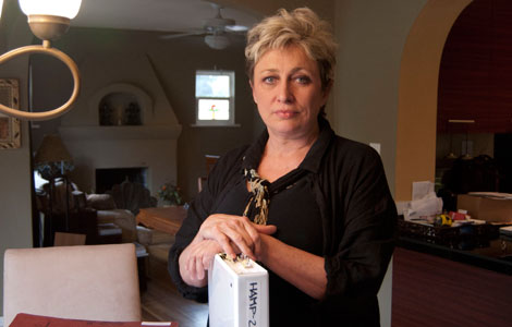 Alexis Burris, in her former San Diego home, with materials she accumulated during her year-long quest for a loan mod. (Paul Kiel and Olga Pierce, ProPublica)