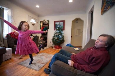 Willie Rembis watches his daughter Cinderella, 4, dance in the living room of their rental home in Warren, Mich. (Jeffrey Sauger for ProPublica)