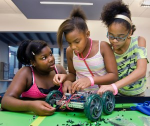 Destnee Walton, 12, from left, Martayllia Copes, 10, and Jordan Miller, 11, all of Kansas City, assemble a robot, July 20, at Science City in Kansas City's Union Station. The KC STEM Alliance (science, technology, engineering and medicine) summer camp hosted a field trip to Science City where campers demonstrated robots they designed, programmed and built using the engineering skills they learned during camp. (Allison Long/Kansas City Star/MCT)