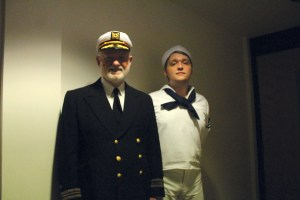 Photo by Kelcey Williams | Dennis Sims and Tyle Cook, playing the captain of the S.S. American and one of the sailors respectively, stand together backstage.