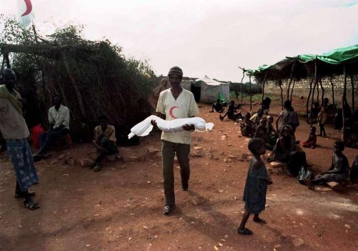 Όταν ο θάνατος ενός παιδιού είναι μια καθημερινότητα: εργαζόμενος στην ανθρωπιστική βοήθεια μεταφέρει για ταφή ένα παιδί που πέθανε σε στρατόπεδο προσφύγων στη Σομαλία, στις 15 Δεκεμβρίου 1992