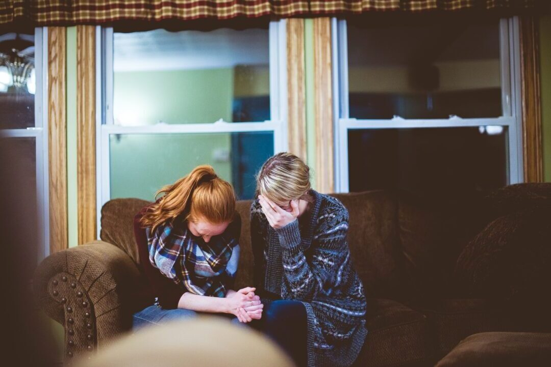 two women seated on a couch bow in tearful prayer