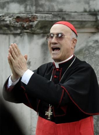 Tarcisio Bertone con traje talar ordinario negro con cordón rojo y la faja roja, con solideo, cruz pectoral y anillo
