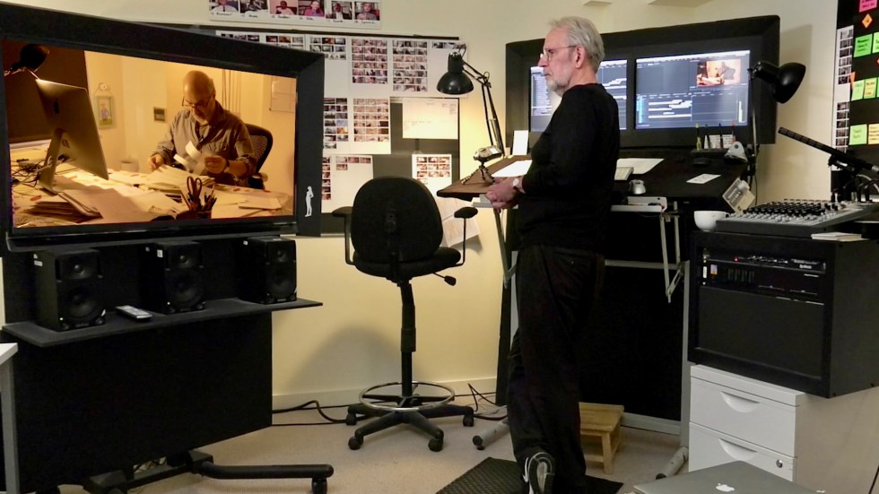 Walter Murch stands at his editing table, watching a scene from his latest documentary, Coup 53.