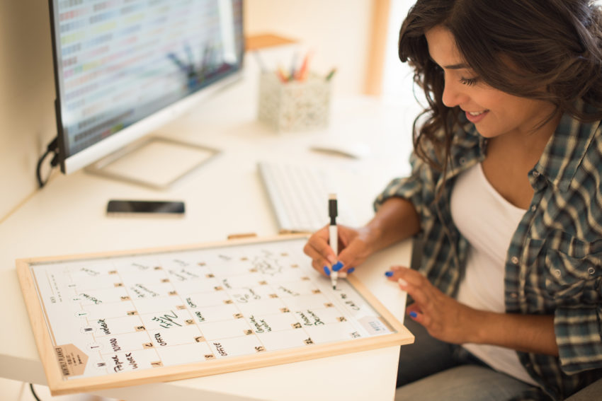 Woman on computer desk wrinting on calendar
