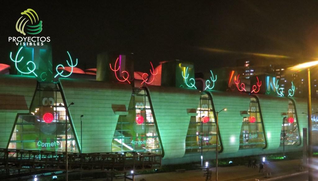 Iluminación con reflectores led verdes, vinilo adhesivo cara de reno y  con estructura liviana circular  recubierta con tela extensiones de led rojas y complementadas con estructuras metálicas bordeadas con manguera color verde y rojo.