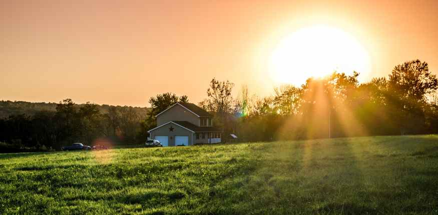 Rising sun over the house in the country
