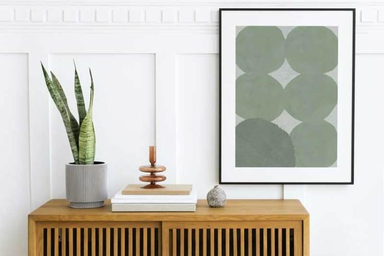 Picture frame mockup hanging above wooden cabinet
