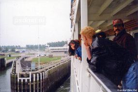 Passagiers op de veerboot Koningin Beatrix kijken over de reling terwijl de dubbeldekker in de fuik van Breskens ligt.