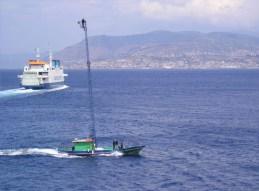 Op de achtergrond vaart de voormalige Zeeuwse veerboot Koningin Beatrix (nu: Tremestieri), op de voorgrond wordt op traditionele manier gevist op zwaardvissen.