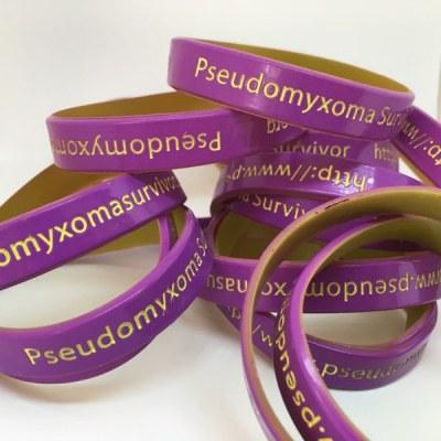 a photo of a pile of Pseudomyxoma Survivor wristbands